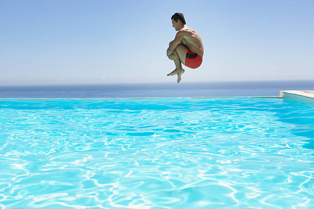 Man leaping into infinity pool stock photo