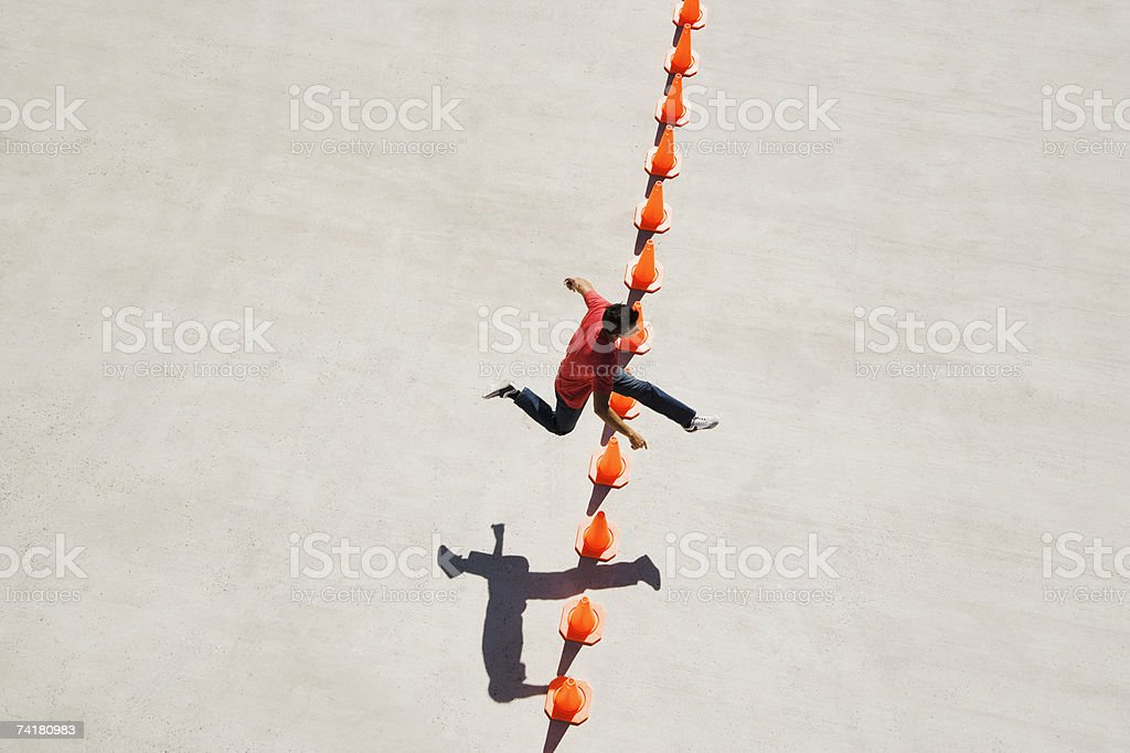 Man leaping over row of traffic cones royalty-free stock photo