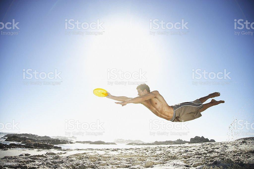 Un homme volant dans l'air sur la plage regardant un Frisbee - Photo