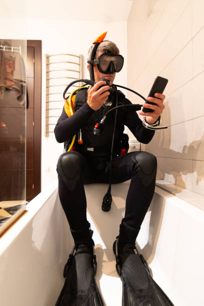 A man learns through online lessons with his smartphone to dive, in the bathtub of his house. Home confinement stock photo