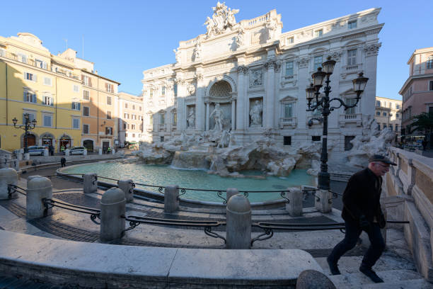 A man leaves the deserted Trevi Fountain, empty today, in Rome, Italy stock photo