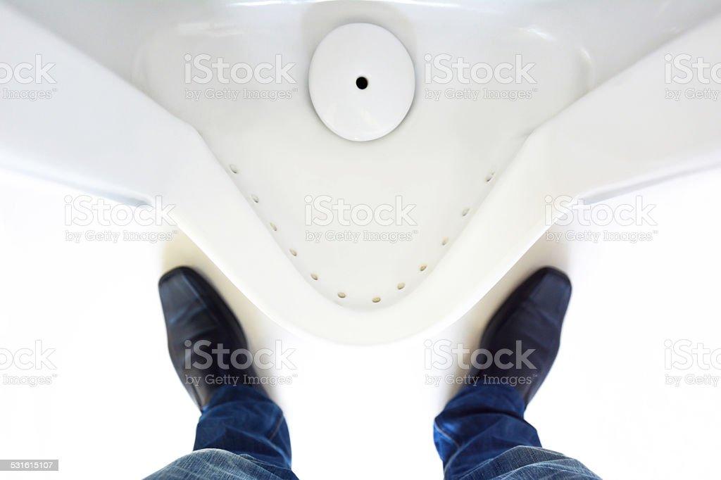 Man legs in front of urinal in men toilet stock photo