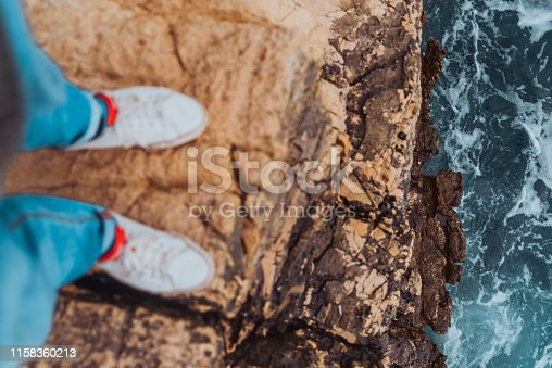 man legs in jeans and white sneakers at the edge of the cliff view of blue stormy sea