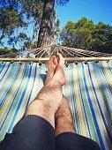 man legs resting on a hammock on vacation