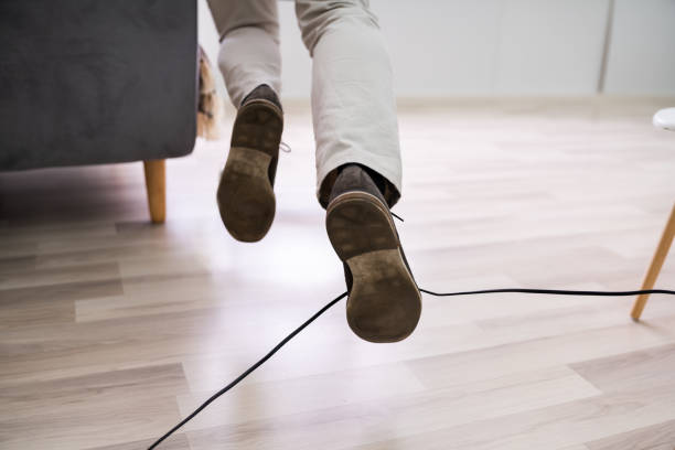 Man Legs Stumbling With An Electrical Cord stock photo