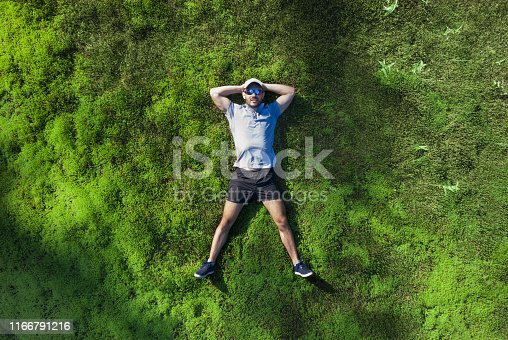 A man lies on a green moss in the forest. View from above