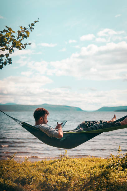 Man lies on a hammock by the lake stock photo