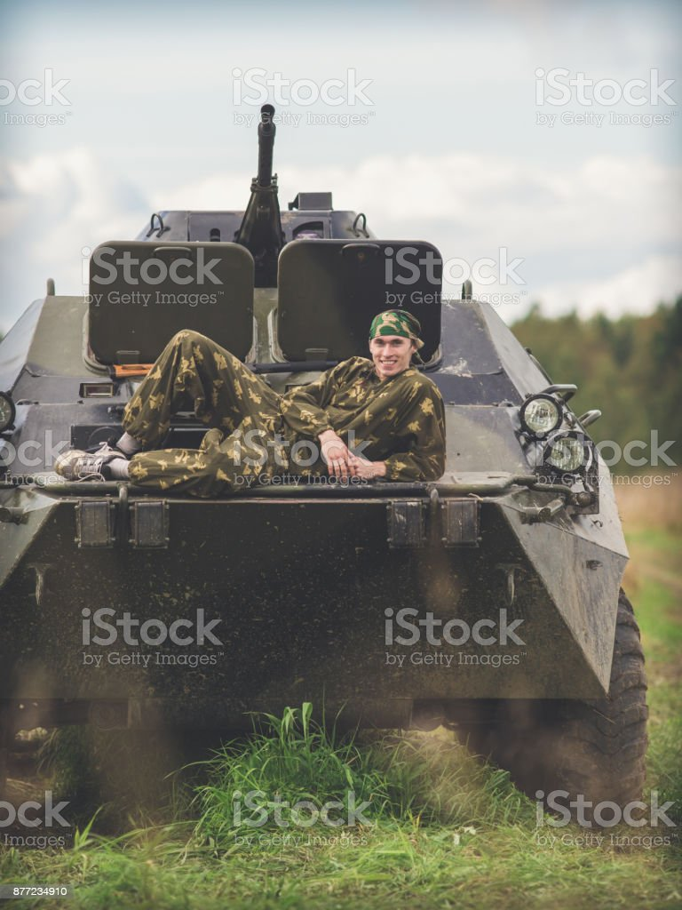 A man lies on a military vehicle in a field stock photo
