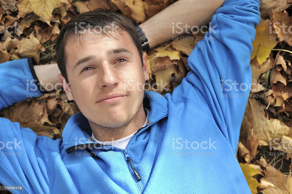 man lies on yellow leaves royalty-free stock photo