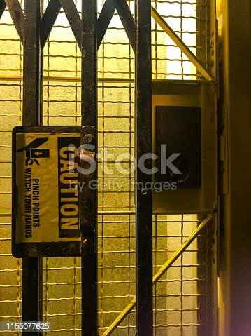 Old single person man lift elevator door with caution