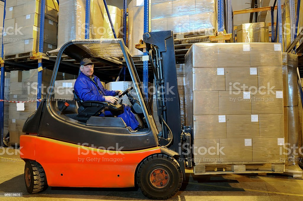 Man lifting a large palate of boxes with a forklift stock photo