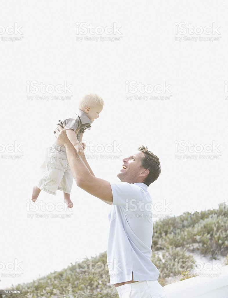 Homem levantando bebê ao ar livre foto de stock royalty-free