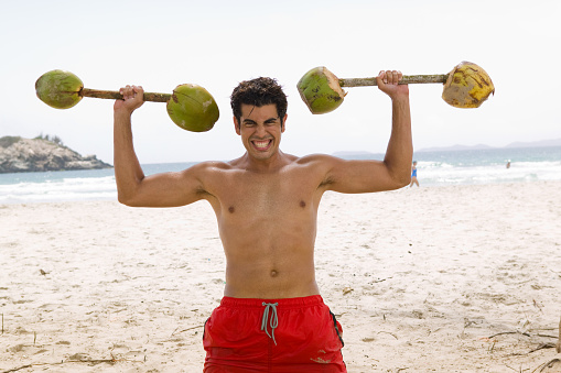 Man lifting coconuts as dumbbells on the beach, smiling portrait