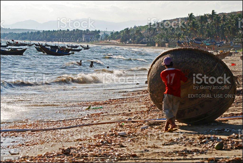 Man lifting coracle on beach stock photo