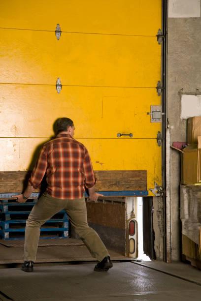 Man lifting door at warehouse Man lifting door at warehouse distribution center stock pictures, royalty-free photos & images