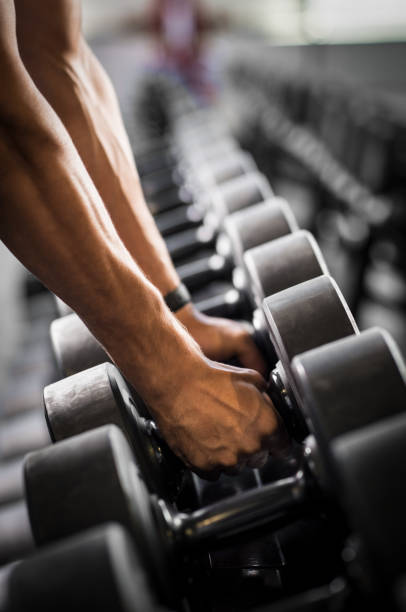 man lifting dumbbells - human limb stock pictures, royalty-free photos & images