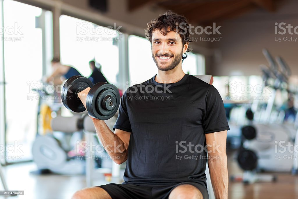 Man lifting weights in a fitness club stock photo