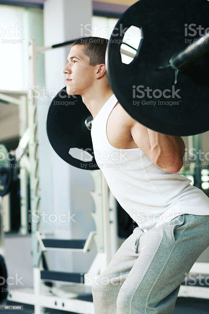 Man lifting weights in gym squats royalty-free stock photo
