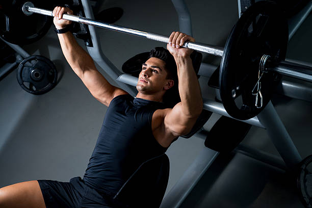 A man lifting weights on a bench press stock photo