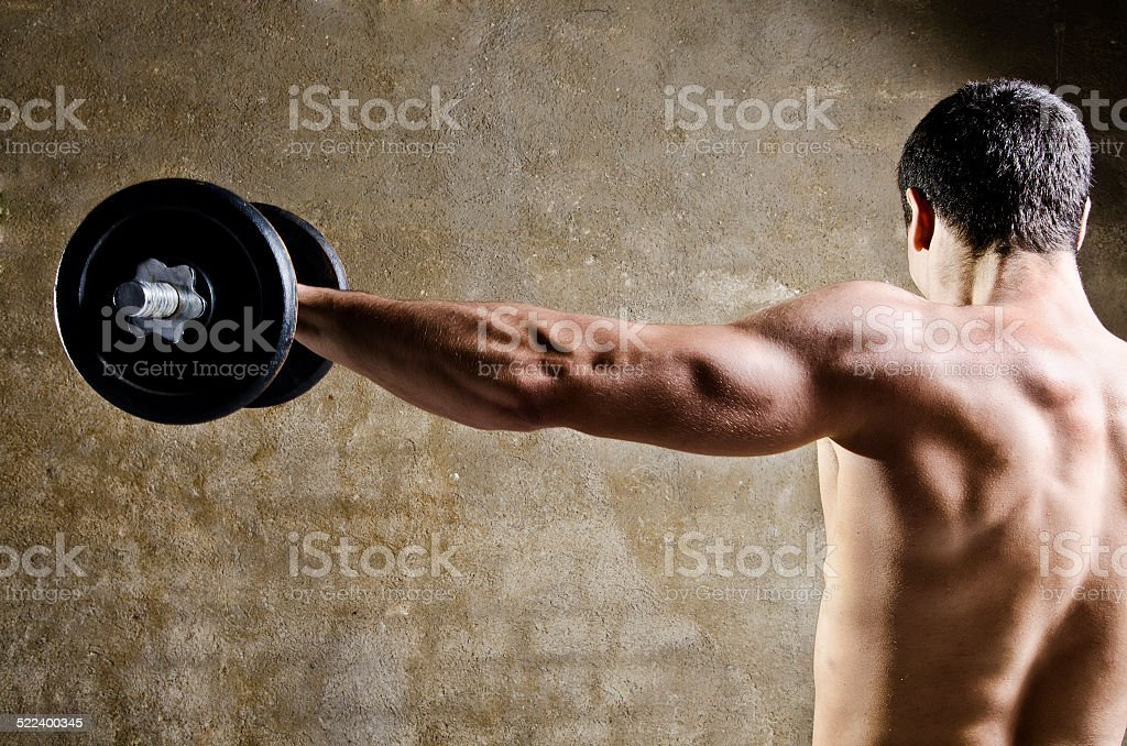 Man lifting weights with shoulders training stock photo
