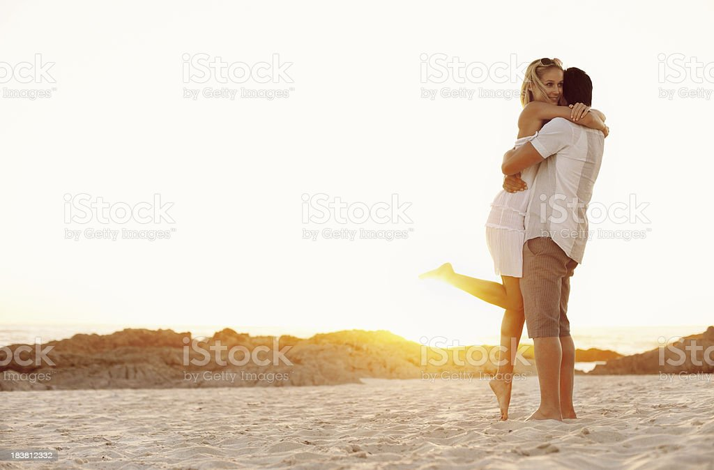Man lifting woman at beach stock photo