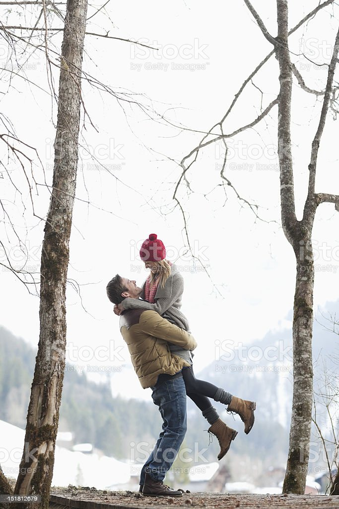 Man lifting woman in snowy woods stock photo