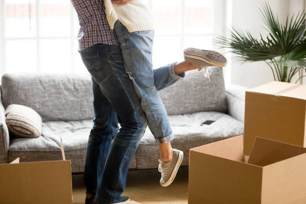 man lifting woman standing among cardboard boxes, close up view - tenant stock photos and pictures