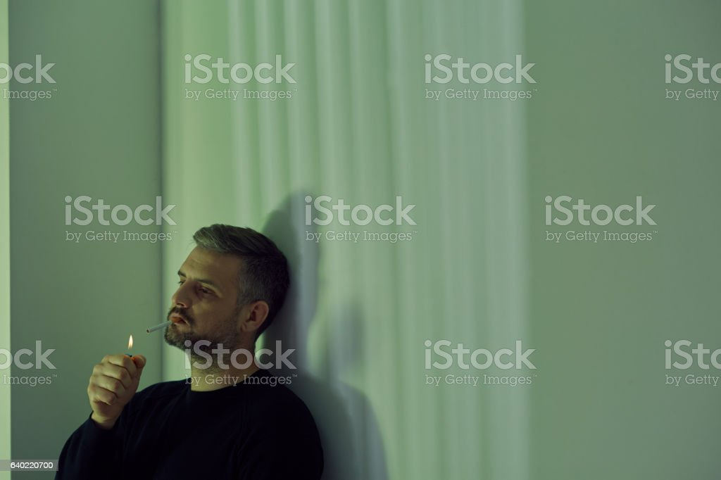 Man lighting a cigarette stock photo