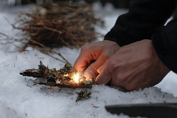 Man lighting a fire in a dark winter forest stock photo