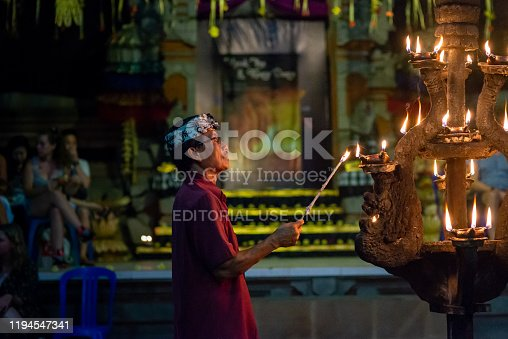 Ubud, Bali, Indonesia - September 3, 2017: Man lighting candles at the beginning of a kecak fire dance ceremony. Taken in the evening with no flash, mostly candle lighting resulting in some image noise.