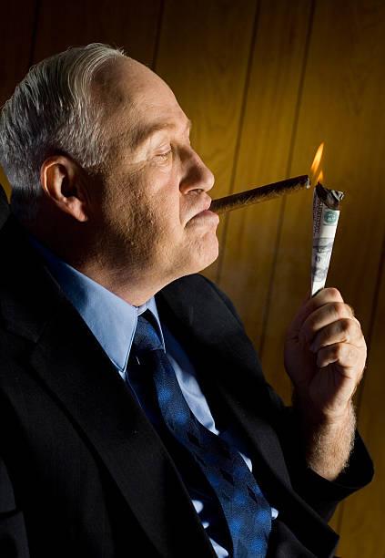 Man lighting cigar with 100 Dollar Bill stock photo