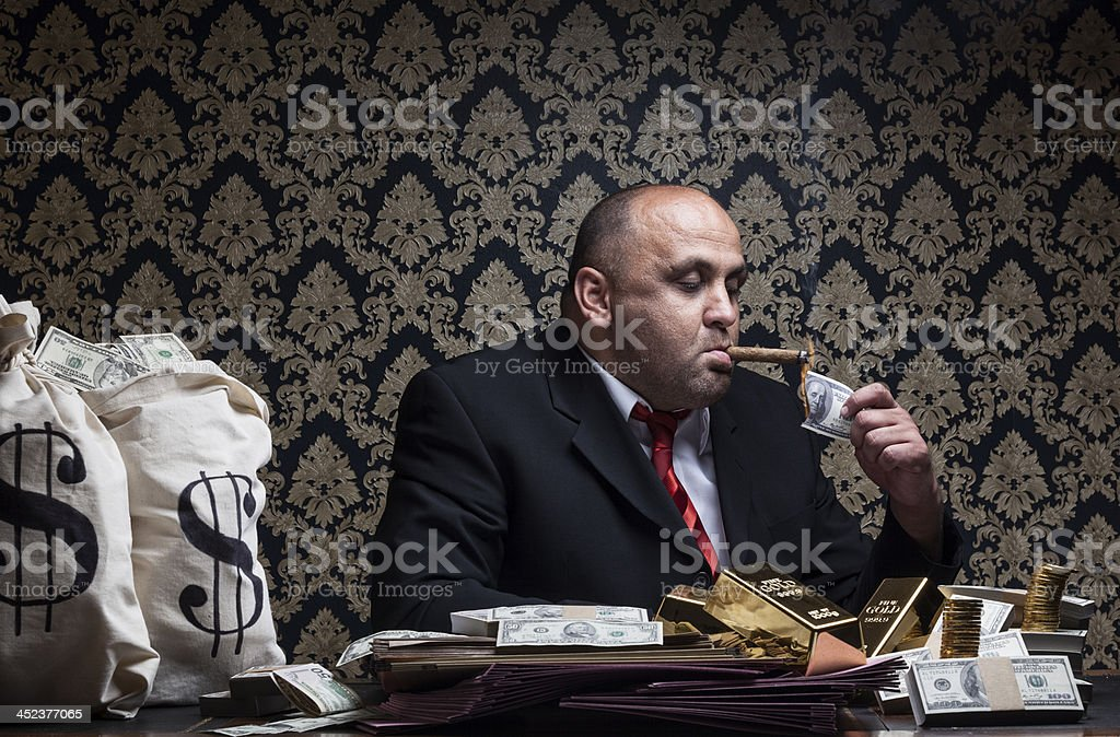 Man lighting cigar with paper money with money bags by him. stock photo