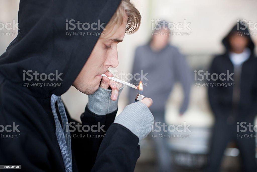 Man lighting marijuana cigarette stock photo