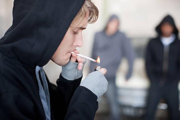 Man lighting marijuana cigarette  marijuana joint stock pictures, royalty-free photos & images