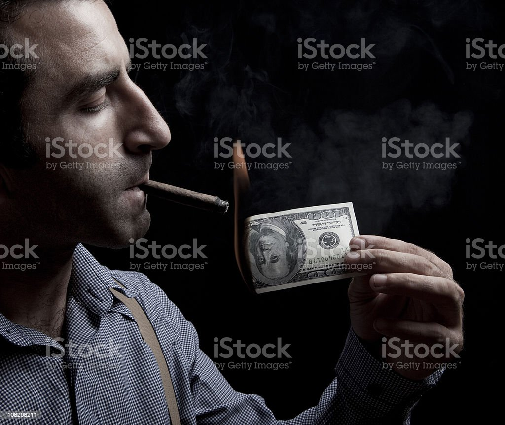 Man lighting up a cigar with US dollar bill royalty-free stock photo