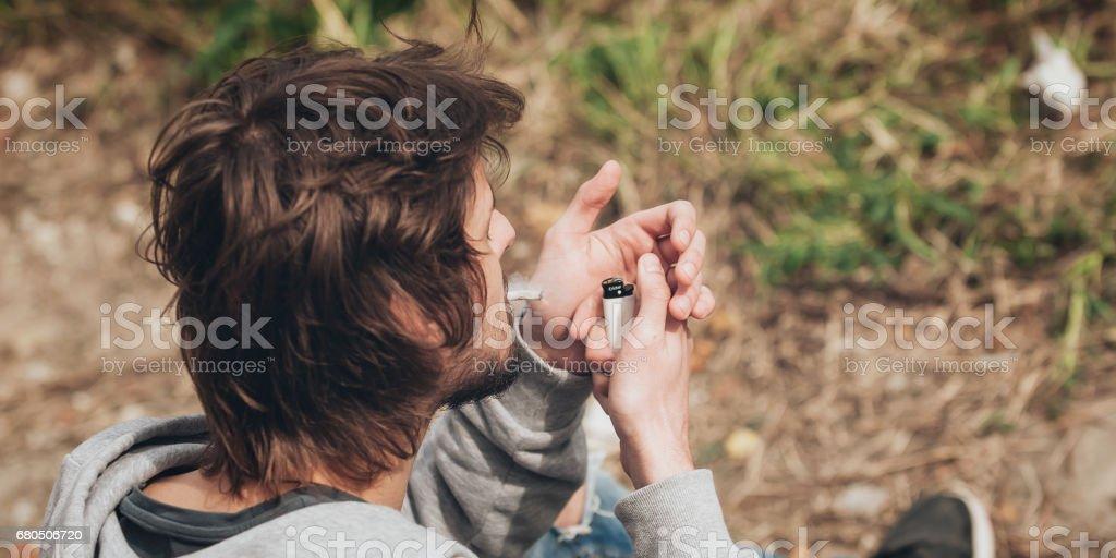 Man lighting up a marihuana or hashish joint cigarette stock photo
