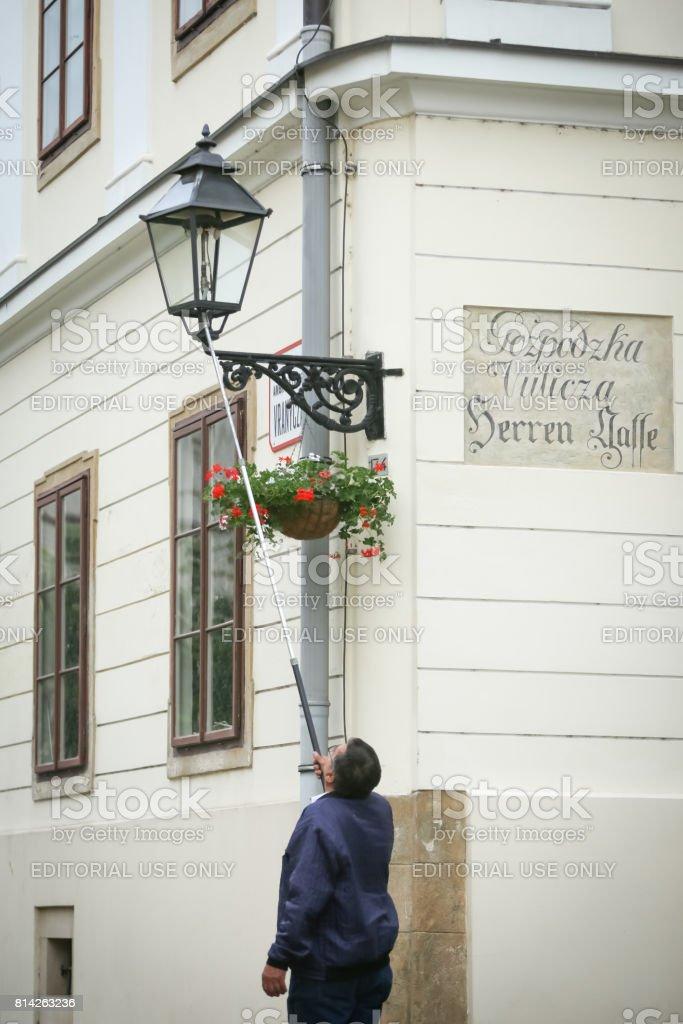 Man lighting up street lamp stock photo
