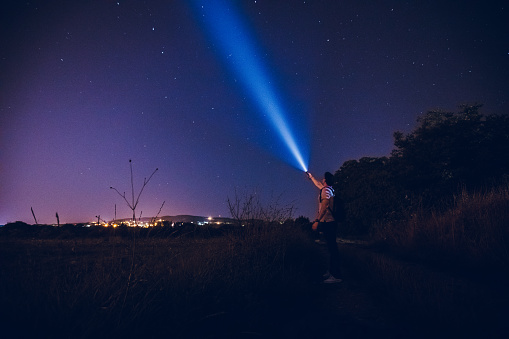 Young caucasian man in the night, with a lantern in the hand doing a beam of light on a sky of stars. Stars exploring.