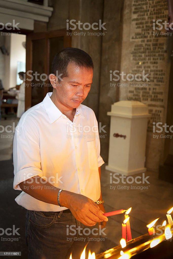 Man Lights Catholic Prayer Candle stock photo