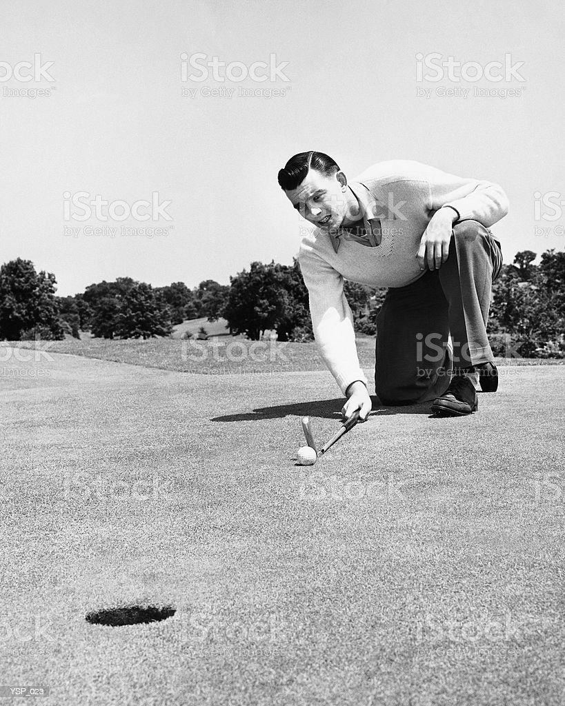 Man lining up golf shot on putting green 免版稅 stock photo