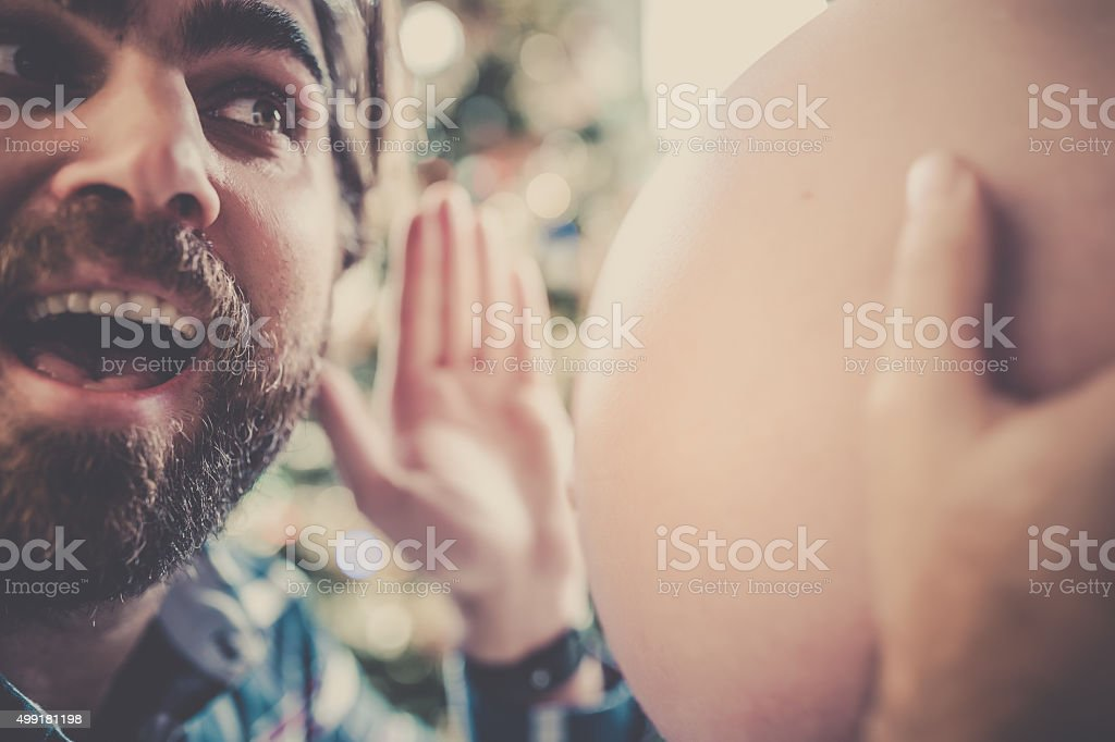 Man Listening and Holding Pregnant Woman Belly stock photo