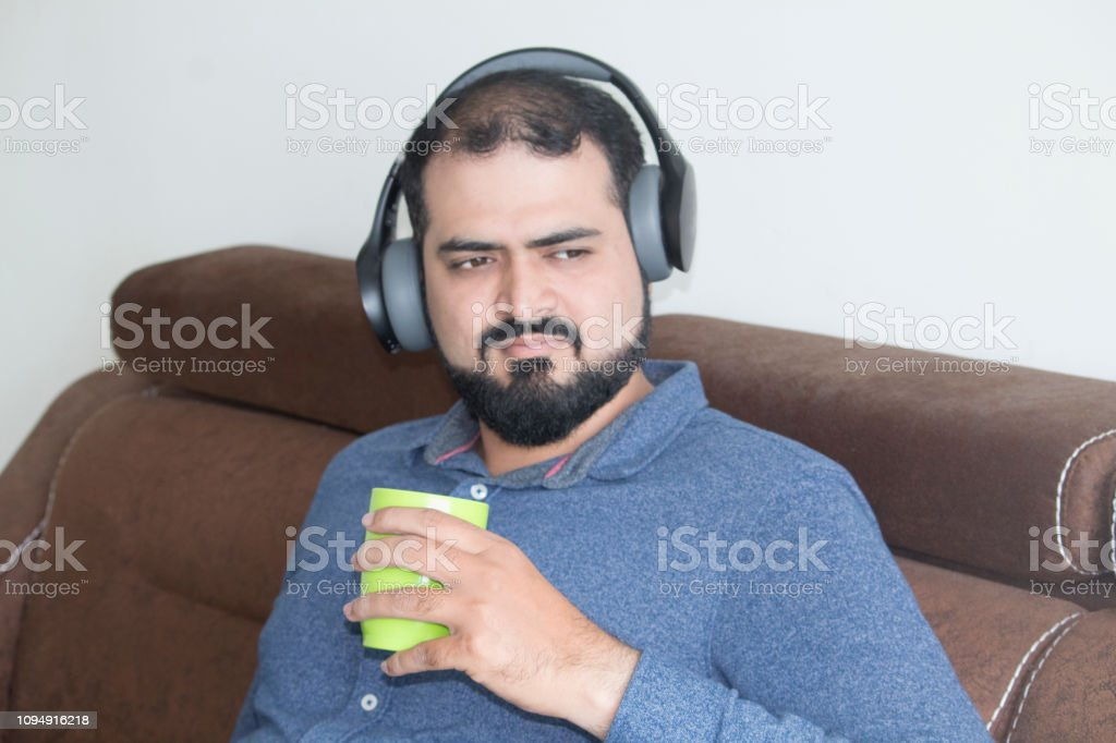 Thoughtful young man listening music and drinking coffee on sofa