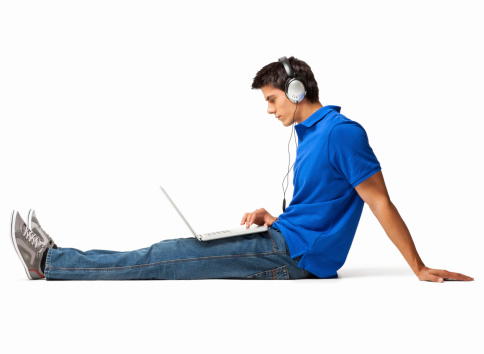 Side view of young man in casuals listening music while surfing net on laptop. Horizontal shot. Isolated on white.
