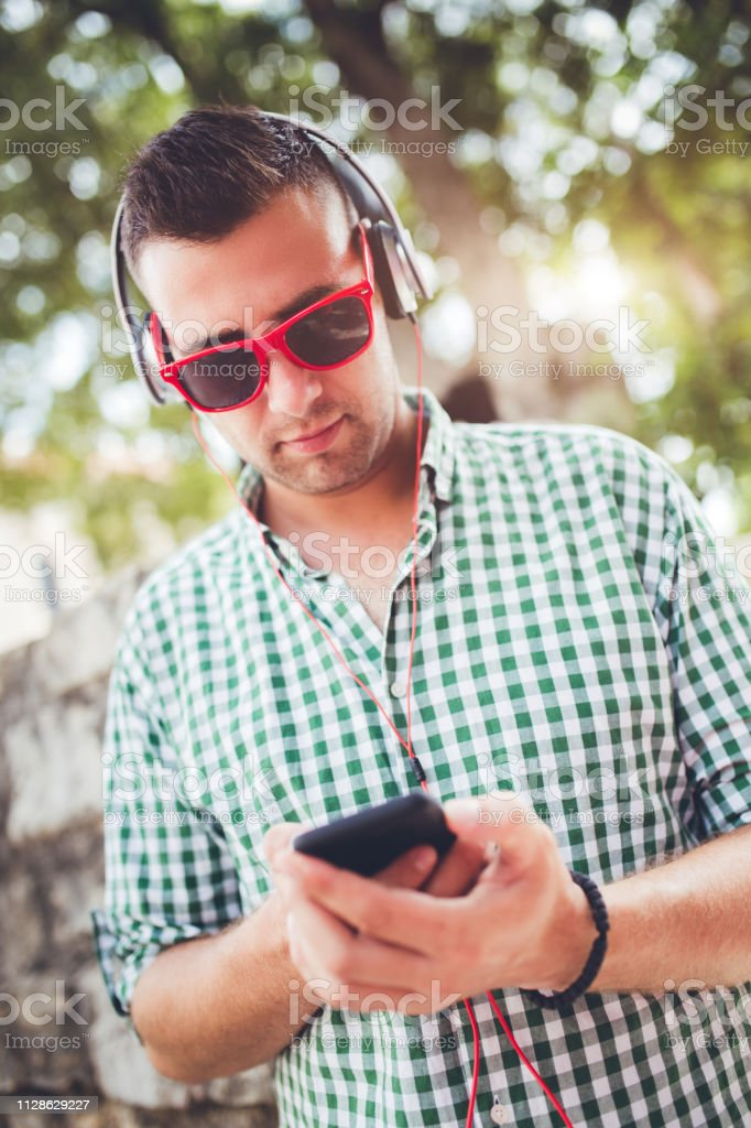 Young man listening music on headphone in Budva Montenegro and...