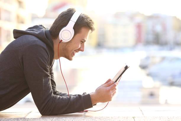 mann, musik hören oder videos ansehen - jugendfilm stock-fotos und bilder