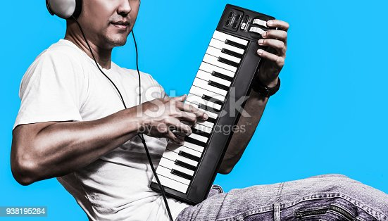 man listening music & playing midi keyboard, isolated on blue