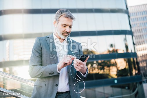 Older man using mobile phone and in-ear headphones outdoors