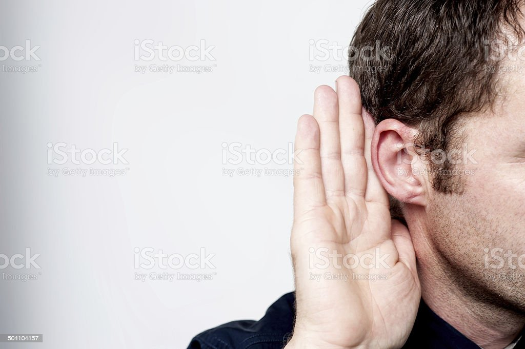 Man listening to gossip Listening male holds his hand near his ear Adults Only Stock Photo