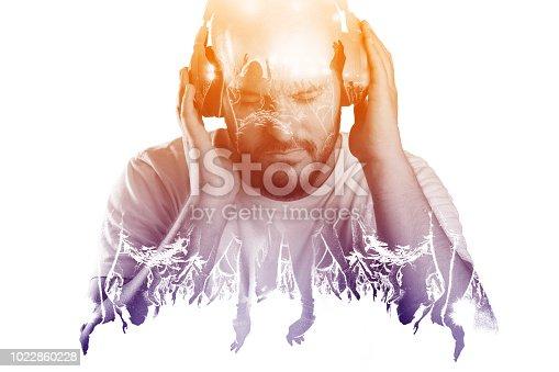 istock Man listening to live music via earphones concept 1022860228