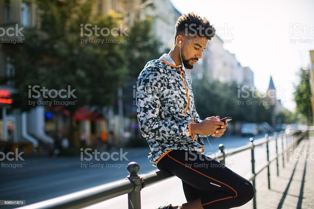 Man listening to music after jogging in city stock photo